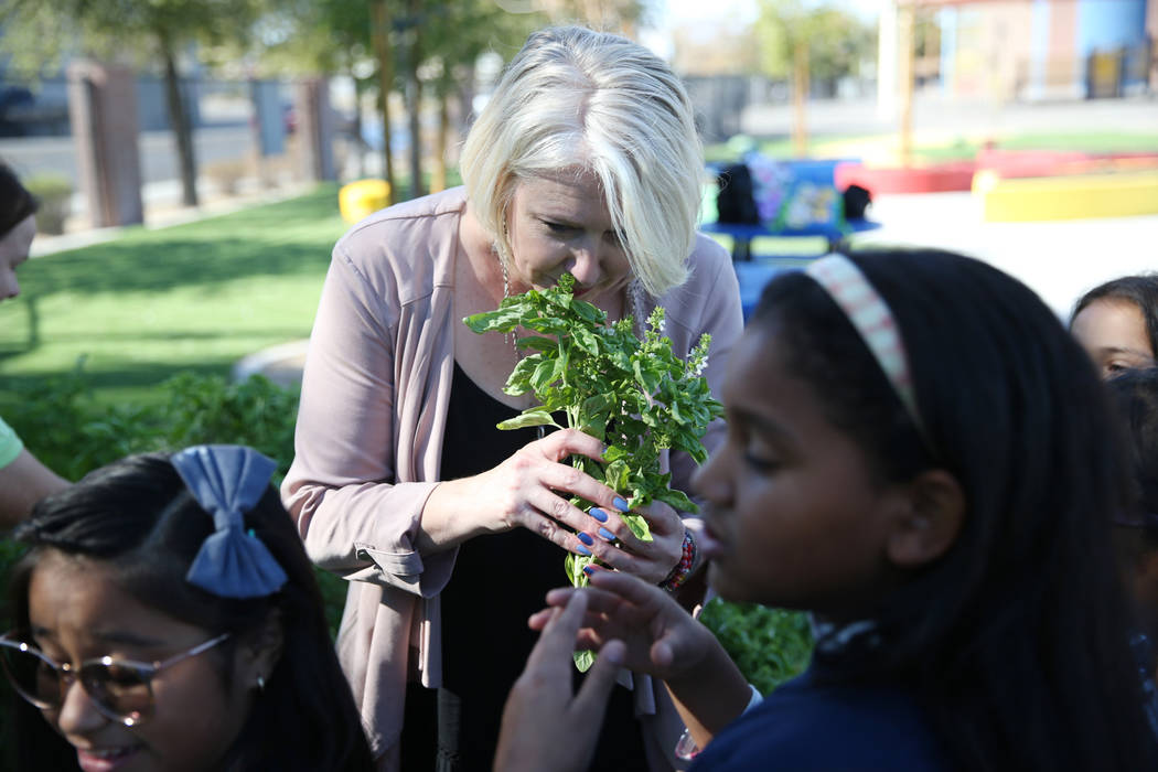 Gina Gavan, centro, fundadora de Project Dinner Table, huele albahaca fresca del jardín de la Escuela Primaria Hollingsworth en Las Vegas, viernes, 7 de septiembre de 2018. Erik Verduzco Las Vega ...