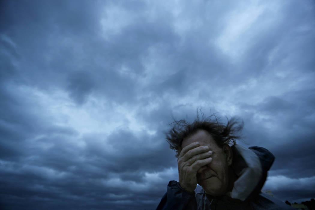 Russ Lewis se cubre los ojos de una ráfaga de viento y una explosión de arena cuando el huracán Florence se acerca a Myrtle Beach, S.C., el viernes 14 de septiembre de 2018. (AP Photo / David G ...