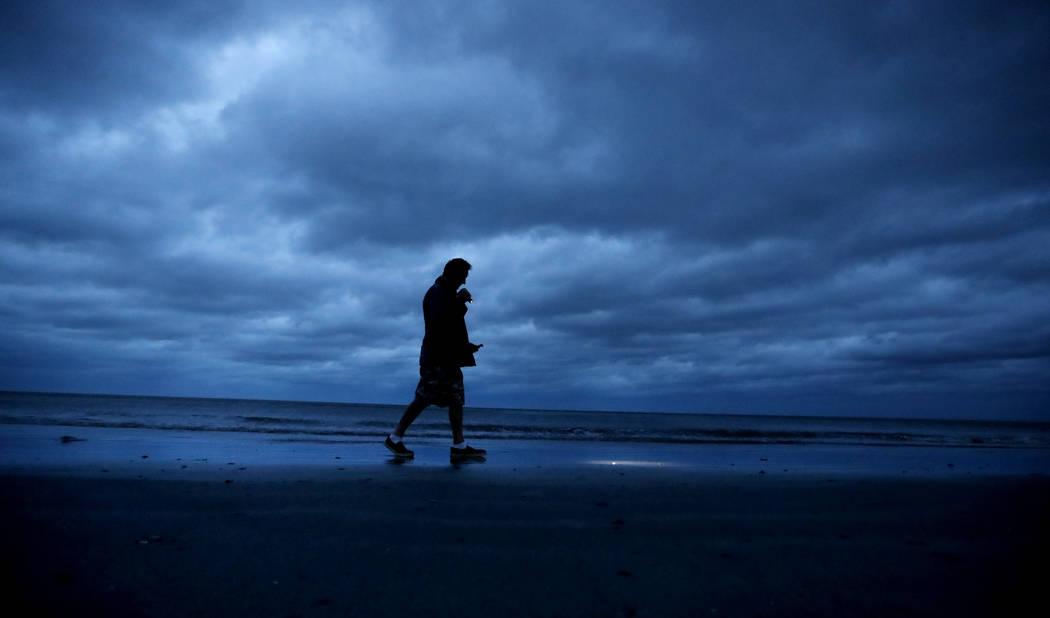 """Russ Lewis busca conchas a lo largo de la playa cuando el huracán Florence se acerca a Myrtle Beach, S.C., el viernes 14 de septiembre de 2018. """"Me levanté esta mañana y no podía escuchar el o ..."""