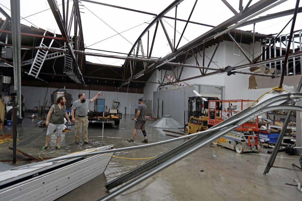 Ethan Hall, a la derecha, Michael Jenkins, centro, y Nash Fralick, a la izquierda, examinan daños a Tidewater Brewing Co. en Wilmington, N.C., después de que el huracán Florence tocó tierra el ...