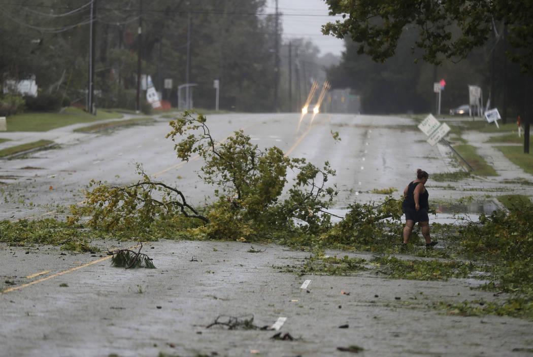Una mujer quita escombros de una carretera en Wilmington, N.C., después de que el huracán Florence tocó tierra el viernes 14 de septiembre de 2018. (AP Photo / Chuck Burton)