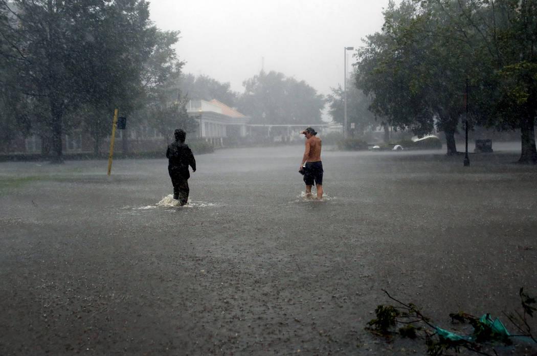 La gente camina a través de las inundaciones causadas por el huracán Florence en el centro de New Bern, N.C., el viernes, 14 de septiembre de 2018. (AP Photo / Chris Seward)