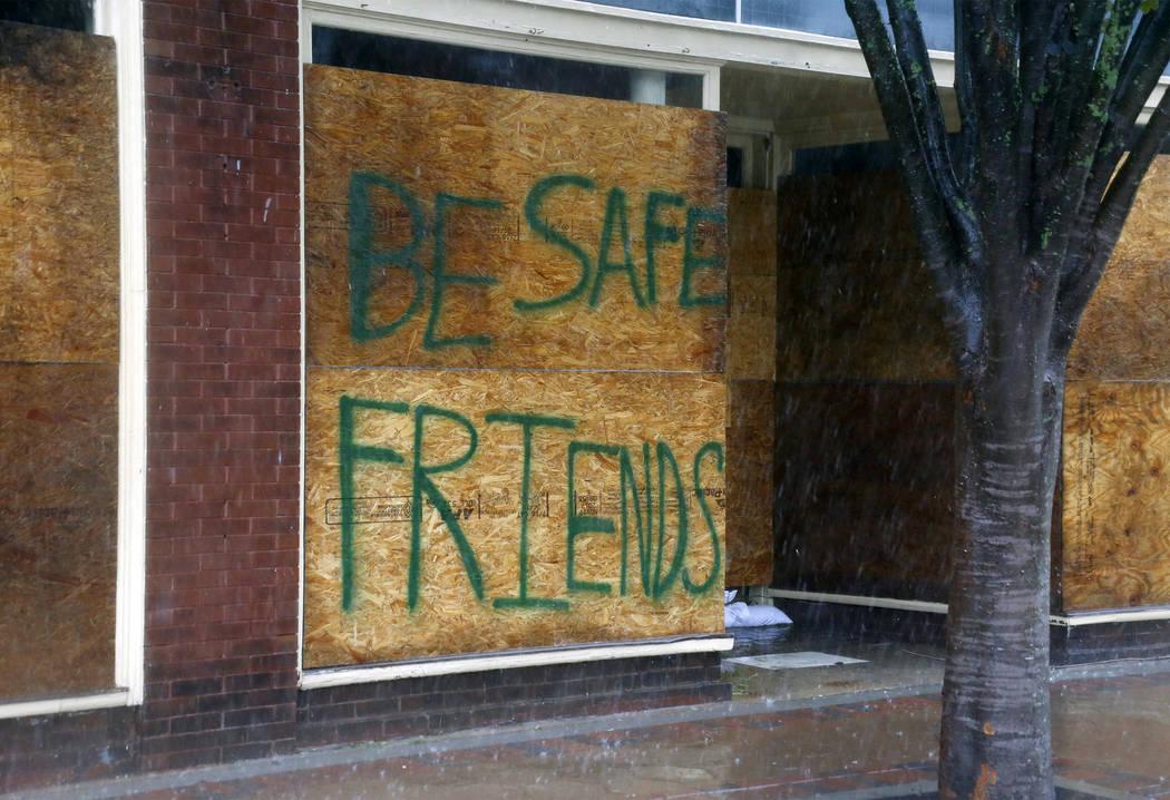 Un mensaje sobre un negocio cerrado alienta a la gente a estar a salvo cuando el huracán Florence golpee el centro de New Bern, N.C., el viernes 14 de septiembre de 2018. (AP Photo / Chris Seward)