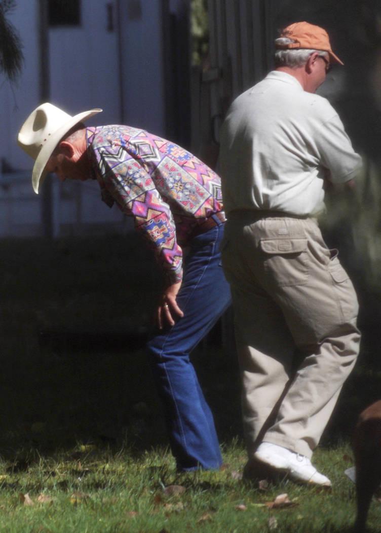 David Mattsen se inclina mientras Tom Dillard, investigador privado de la propiedad de Ted Binion, pasa junto a él durante una búsqueda de tesoros enterrados en Pahrump en septiembre de 2000. No ...