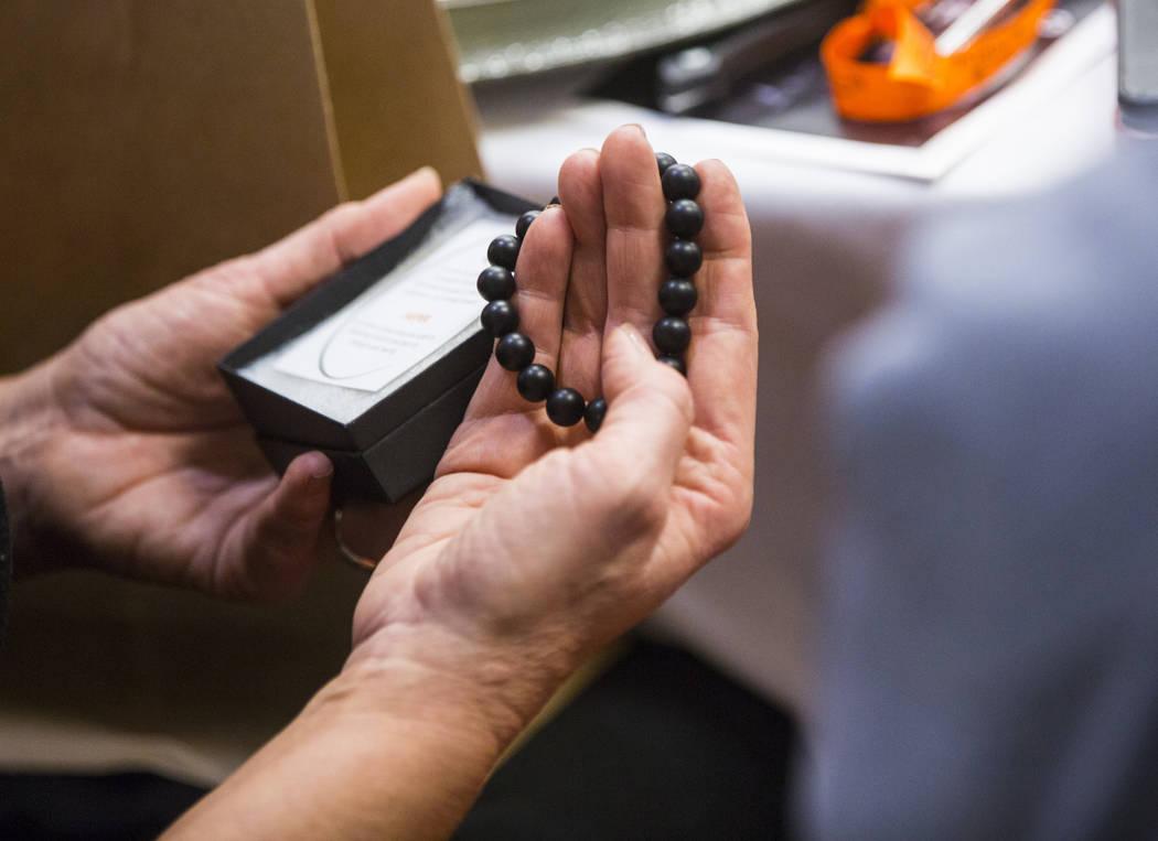 Un sobreviviente del 1 de octubre sostiene un brazalete de ónice entregado como obsequio en el Sunrise Hospital and Medical Center en Las Vegas el viernes 14 de septiembre de 2018. (Chase Stevens ...