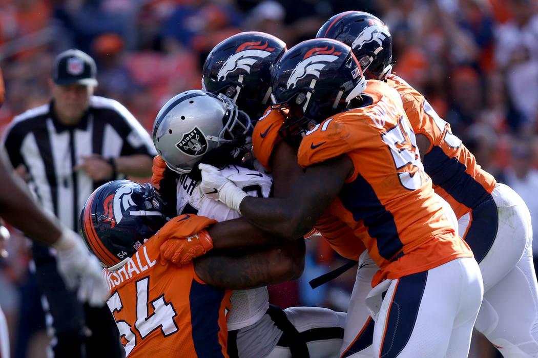 El corredor de los Oakland Raiders, Marshawn Lynch (24), es tackleado por el linebacker de los Denver Broncos: Brandon Marshall (54), el linebacker Todd Davis (51) y otros durante la segunda mitad ...