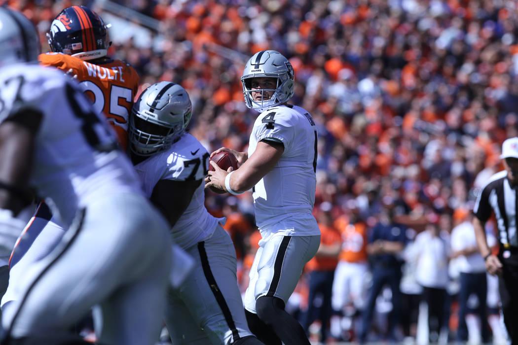 El mariscal de campo de los Oakland Raiders Derek Carr (4) busca pasar el balón durante la primera mitad de su juego de la NFL contra los Denver Broncos en Denver, Colorado, el domingo 16 de sept ...