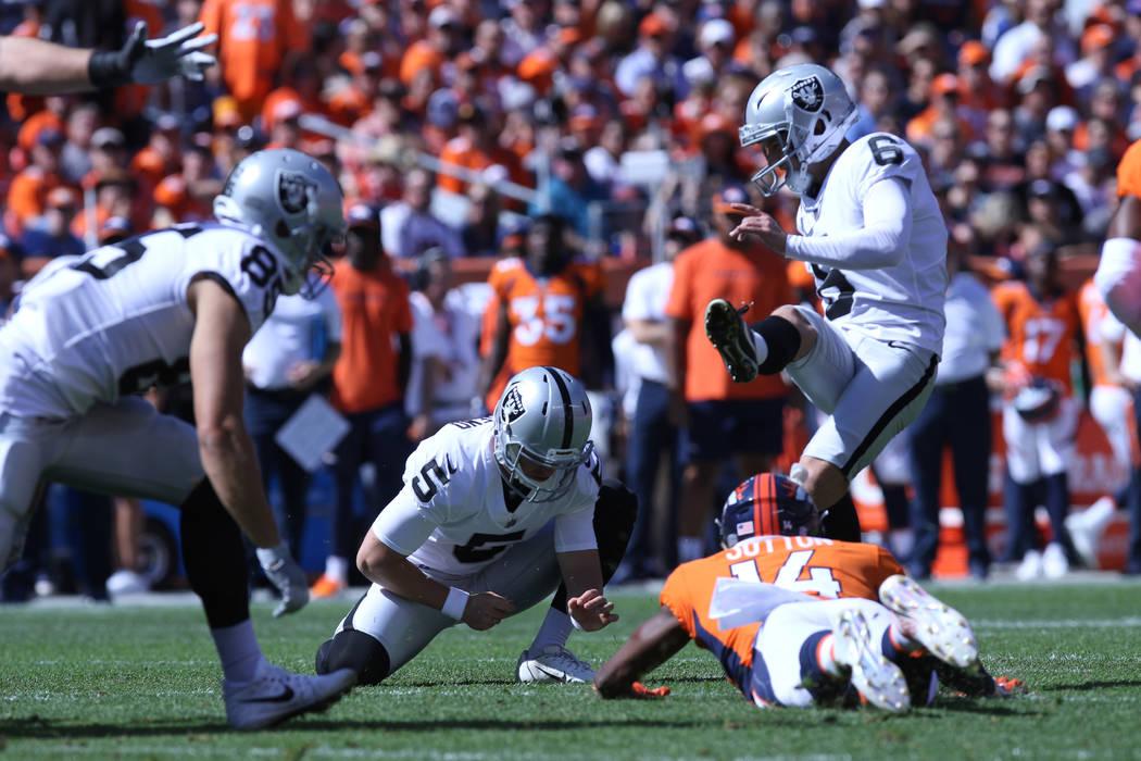 El pateador de los Oakland Raiders, Mike Nugent (6), patea un gol de campo y patea Johnny Townsend (5) mientras el receptor abierto de Denver Broncos, Courtland Sutton (14), entra por un bloqueo d ...