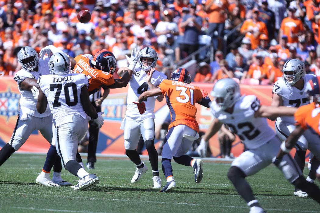 El mariscal de campo de los Oakland Raiders Derek Carr (4) lanza el balón durante la primera mitad de su partido de la NFL contra los Denver Broncos en Denver, Colorado, el domingo 16 de septiemb ...