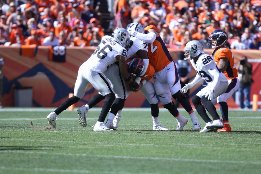 El linebacker de los Oakland Raiders, Derrick Johnson (56) y el tackle defensivo Maurice Hurst (73), bloquean al mariscal de campo de los Denver Broncos, Case Keenum (4) durante la primera mitad d ...