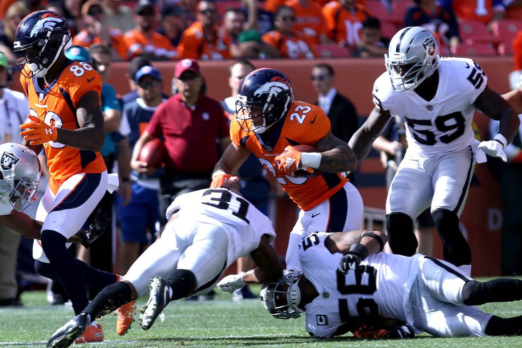 El corredor de los Denver Broncos, Devontae Booker (23), corre con el balón más allá del defensa de los Oakland Raiders, Marcus Gilchrist (31), el linebacker Derrick Johnson (56) y el linebacke ...