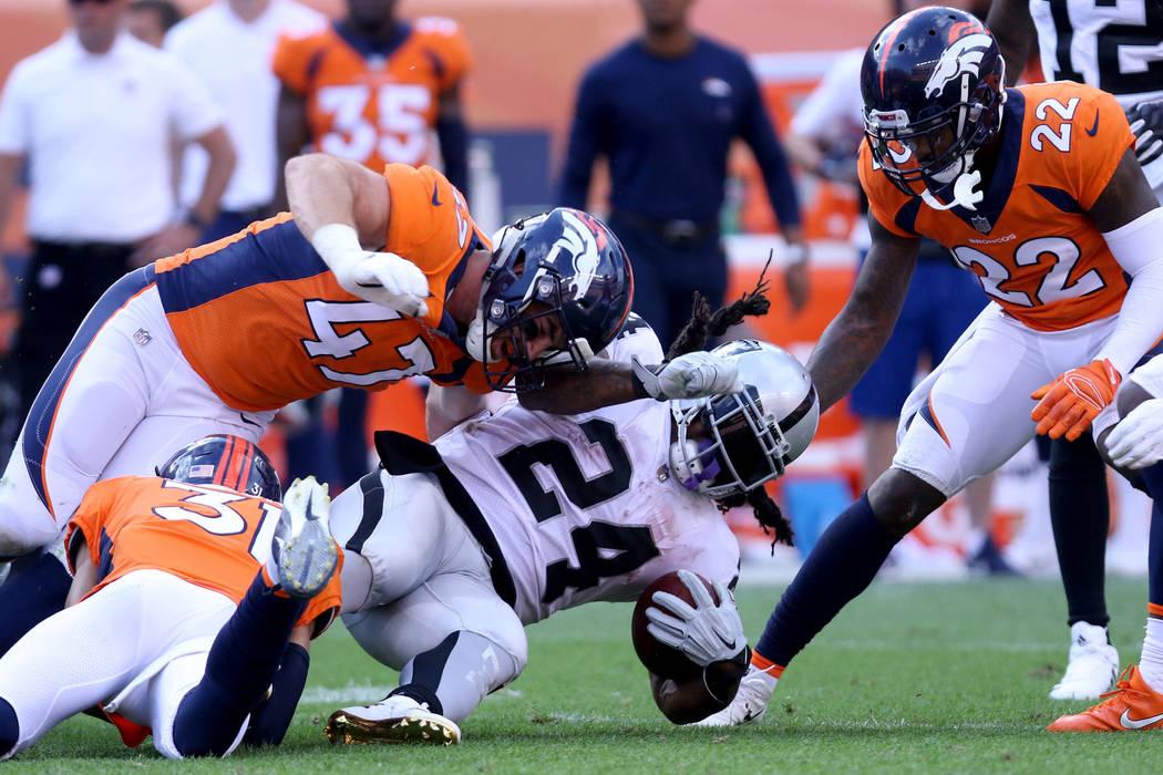 El corredor de los Oakland Raiders, Marshawn Lynch (24) es tackleado por Josey Jewell (47) y el defensa Justin Simmons (31) durante la segunda mitad de su juego de la NFL en Denver, Colorado, el d ...