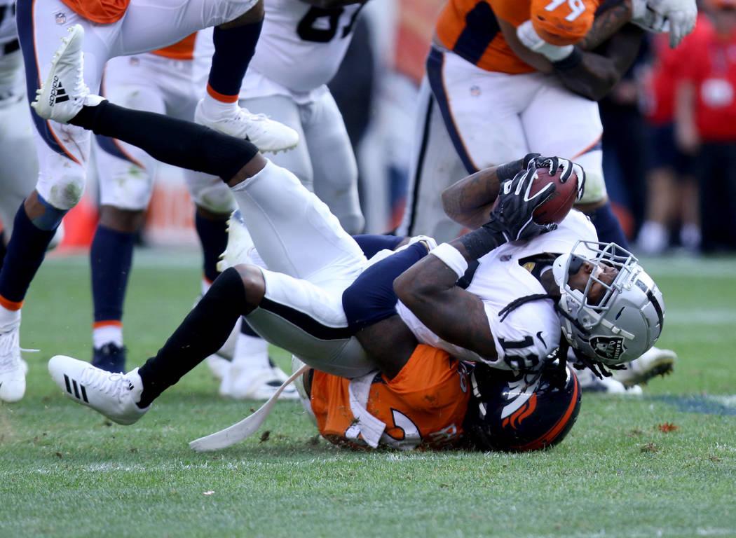 El receptor abierto de los Oakland Raiders, Martavis Bryant (12) es tackleado por Bradley Roby (29) durante la segunda mitad de su juego de la NFL en Denver, Colorado, el domingo 16 de septiembre ...