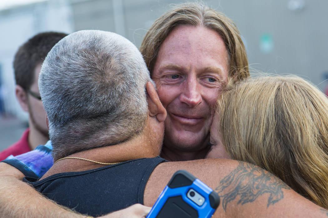 Timothy Tyler, en el centro, abraza a su primo, Dave Phelps, a la izquierda, y su amiga Hilary después de visitar una casa intermedia para quitarse el monitor de tobillo al completar su sentencia ...