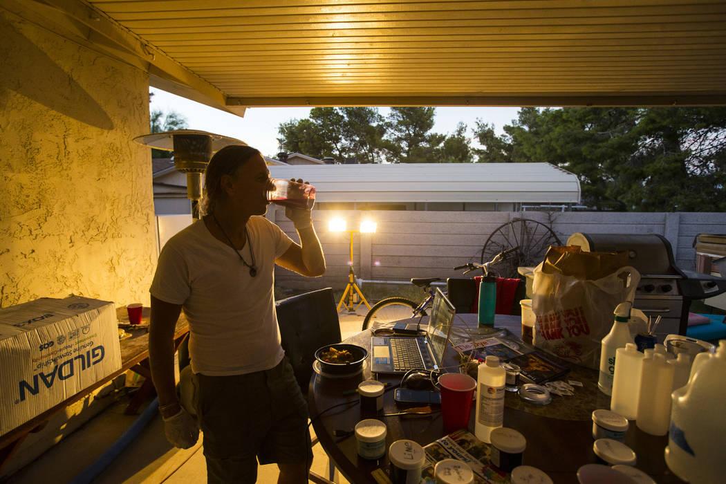 Timothy Tyler bebe un sorbo de jugo de remolacha mientras se relaja con amigos y familiares después de visitar una casa intermedia para quitarse el monitor de tobillo al completar su sentencia el ...