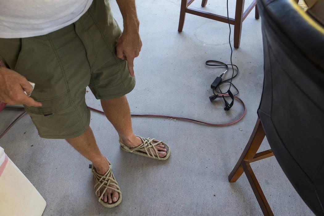 Timothy Tyler apunta a sus sandles después de visitar una casa intermedia para quitarse el monitor de tobillo al completar su sentencia el 30 de agosto de 2018. Tyler fue condenado originalmente ...