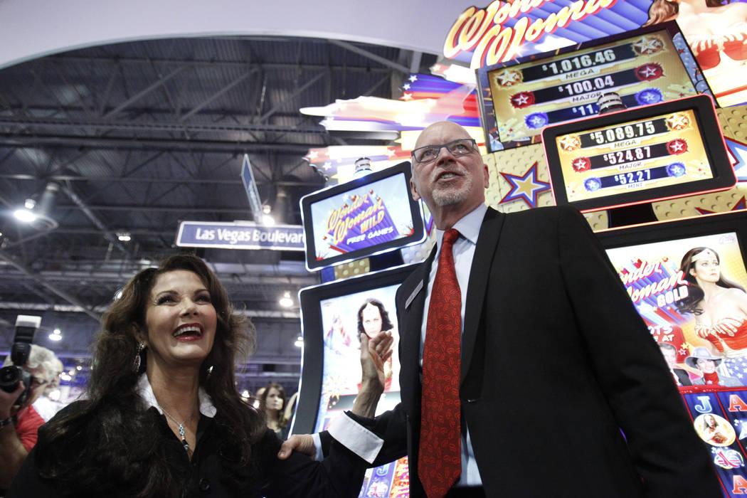 """Lynda Carter, izquierda, estrella de la serie de televisión """"Wonder Woman"""", y Richard Haddrill, CEO de Bally Technologies, posan para las fotos en la presentación de la máquina tragamonedas Bal ..."""