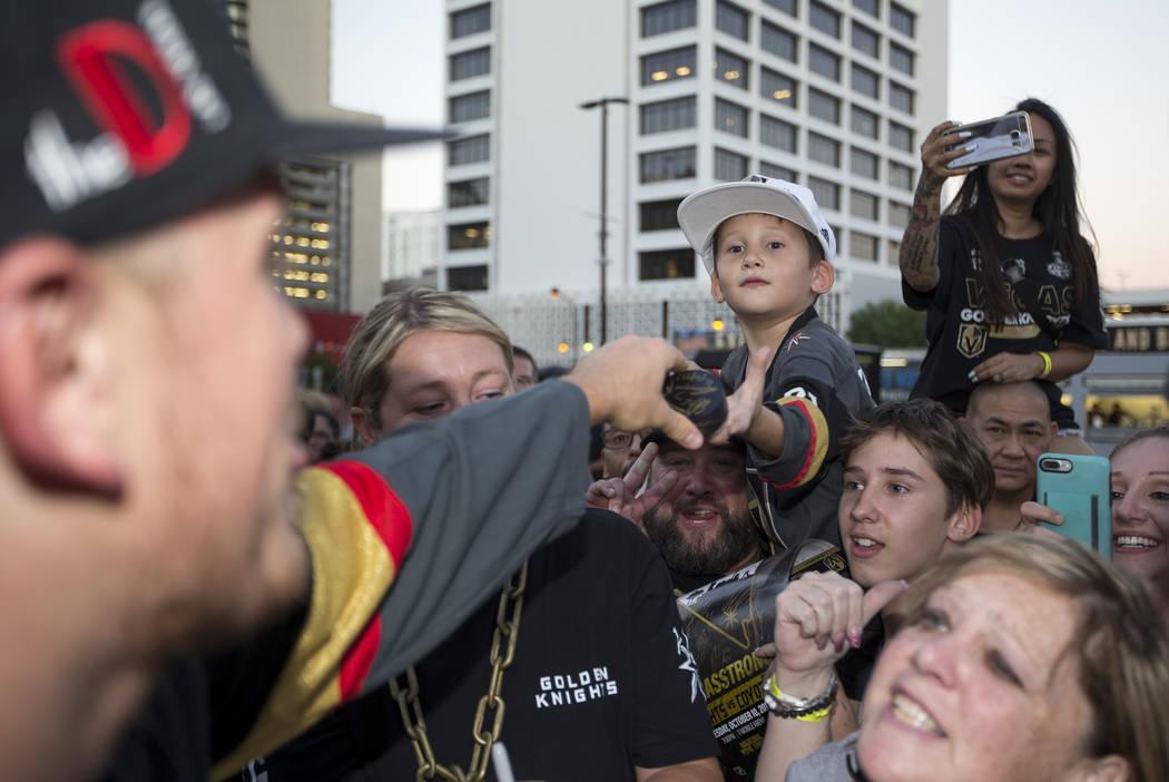 Jaxon Galvan, de 6 años, recibe su puck autografiado por el defensor de los Vegas Golden Knights, Nate Schmidt, izquierda, durante una fiesta de los fans de los Vegas Golden Knights en el Centro ...