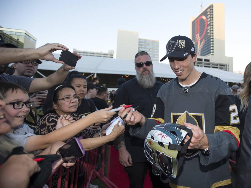 El portero de Vegas Golden Knights, Marc-André Fleury (29), a la derecha, firma un casco para Anthony Mora, a la izquierda, durante una fiesta de fans de Vegas Golden Knights en el Centro de Even ...