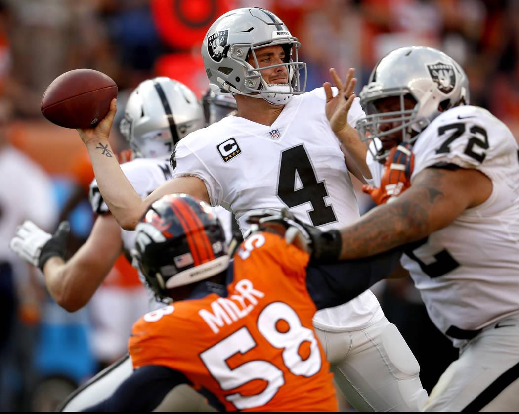 El mariscal de campo de los Oakland Raiders, Derek Carr (4), lanza mientras el linebacker de los Denver Broncos, Von Miller (58), lo persigue durante la segunda mitad de un partido de fútbol amer ...