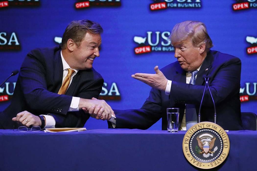 El presidente Donald Trump, a la derecha, le da la mano al senador Dean Heller, republicano por Nevada, durante una mesa redonda sobre la reforma tributaria el sábado 23 de junio de 2018 en Las V ...