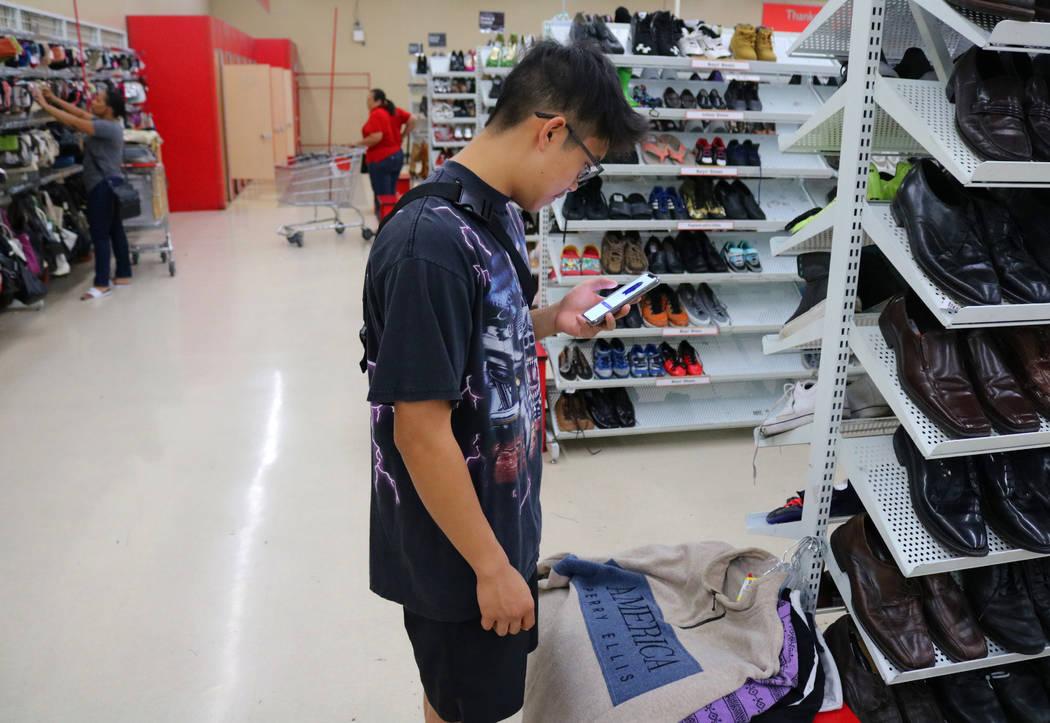 Reanu Elises busca el valor de sus posibles compras en su teléfono en la tienda de ahorro Savers en la intersección de West Sahara Avenue y South Decatur Boulevard en Las Vegas, el miércoles 15 ...