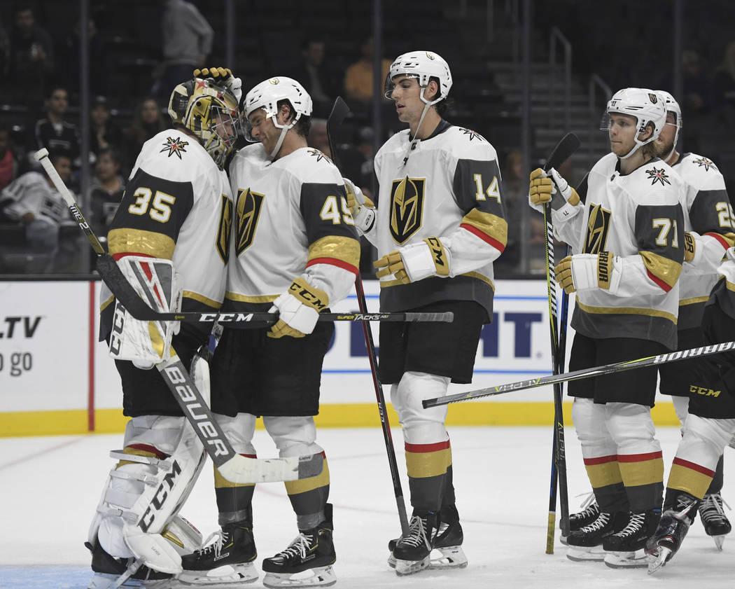 El portero de los Golden Knights de Las Vegas, Óscar Dansk, de Suecia, izquierda, es felicitado por el defensa Jake Bischoff (45) después de que los Golden Knights derrotaran a Los Ángeles King ...