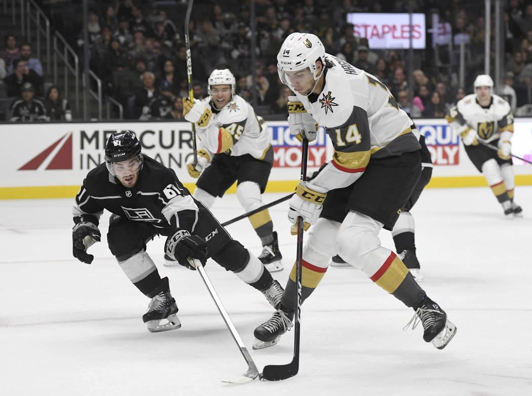 El defensor de los Vegas Golden Knights, Nicolás Hague (14), dispara contra el defensor de Los Ángeles Kings, Sean Walker (61), durante el segundo período de un juego de hockey NHL de pretempor ...