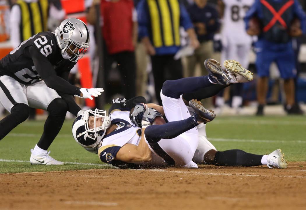 El receptor abierto de Los Ángeles Rams, Cooper Kupp (18), se aferra al balón luego de una atrapada mientras el defensa de los Oakland Raiders, Leon Hall (29), observa durante la primera mitad d ...