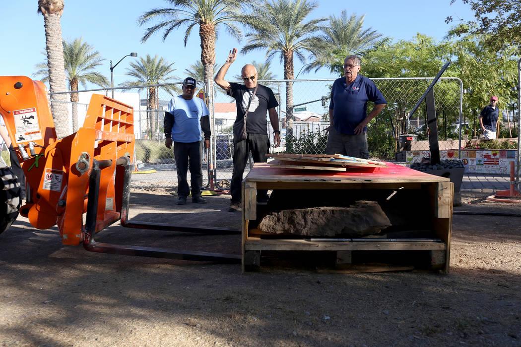 José Cernes, desde la izquierda, el artista Bobby Jacobs, en el centro, y David Schember, supervisan el movimiento de la base de una escultura de piedra diseñada por Jacobs al Healing Garden en ...