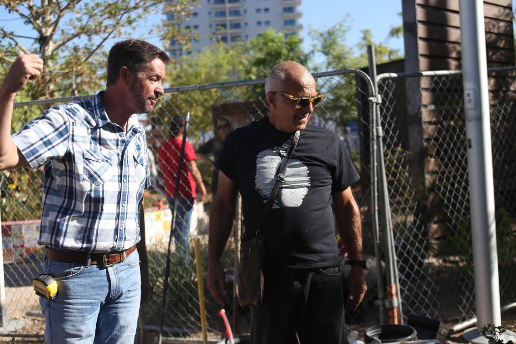Jay Pleggenkuhle, a la izquierda, propietario de Stone Rose Landscapes que opera el Healing Garden, habla con el artista Bobby Jacobs mientras supervisan la instalación de una escultura de piedra ...