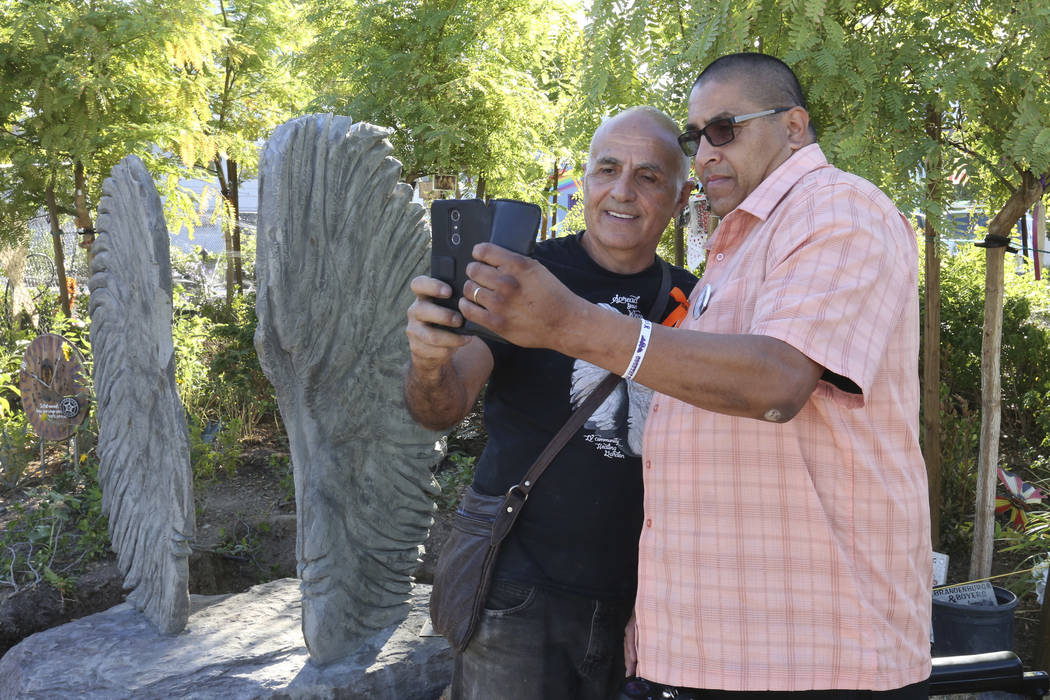 Bobby Jacobs, izquierda, artista del norte de Nueva York, y Daniel Rosales, superviviente del tiroteo del 1 de octubre, se toman una selfie junto a una escultura, a la izquierda, de dos alas de á ...