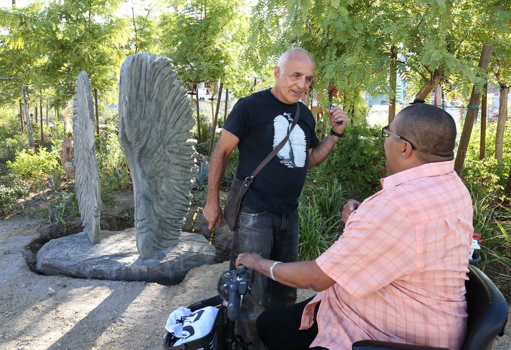 Bobby Jacobs, izquierda, artista del norte de Nueva York, conversa con Daniel Rosales, superviviente del tiroteo del 1 de octubre, junto a su escultura, izquierda, de dos alas de ángel separadas ...