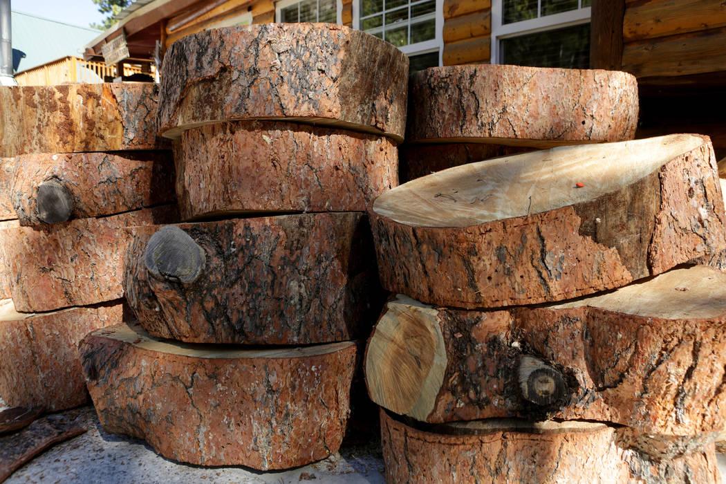 Las rondas de un pino ponderosa de 100 pies de alto que se estima tenía 300 años de edad, yacen apiladas frente a la casa de Rose Meranto en Mount Charleston el lunes 17 de septiembre de 2018, d ...