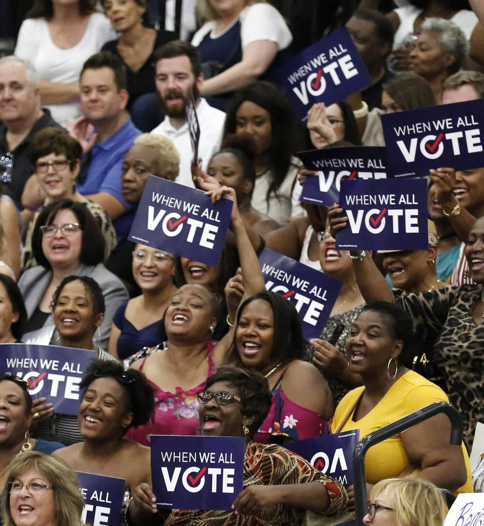 Los asistentes a la reunión aplauden cuando la ex primera dama Michelle Obama habla durante una manifestación de inscripción de votantes el domingo 23 de septiembre de 2018 en Las Vegas. Obama ...