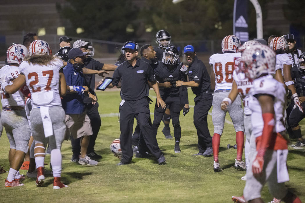 Los entrenadores intentan romper una pelea en el tercer trimestre de una partida en el juego de Liberty Patriots contra los Desert Pines Jaguars el viernes 21 de septiembre de 2018 en la Escuela P ...