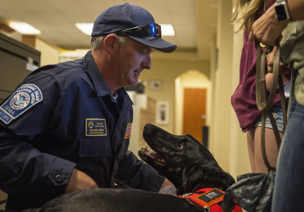 Mike Porter del Departamento de Bomberos de Henderson saluda a su perro, Allie, mientras Nevada Task Force 1 regresa de las áreas afectadas por el huracán Florence en Las Vegas, el lunes 24 de s ...