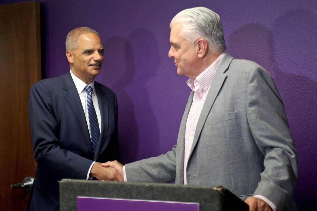 El comisionado Steve Sisolak le da la mano al ex fiscal general Eric Holder, a la izquierda, después de que lo respaldara formalmente como gobernador en las oficinas locales 1107 del Servicio Int ...