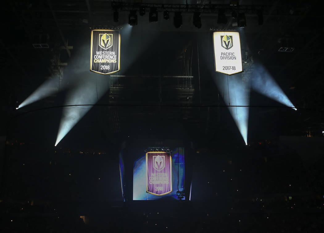 Las banderas de los campeonatos de la División del Pacífico y la Conferencia del Oeste se levantan durante un juego de apertura de la temporada entre los Golden Knights y los Philadelphia Flyers ...