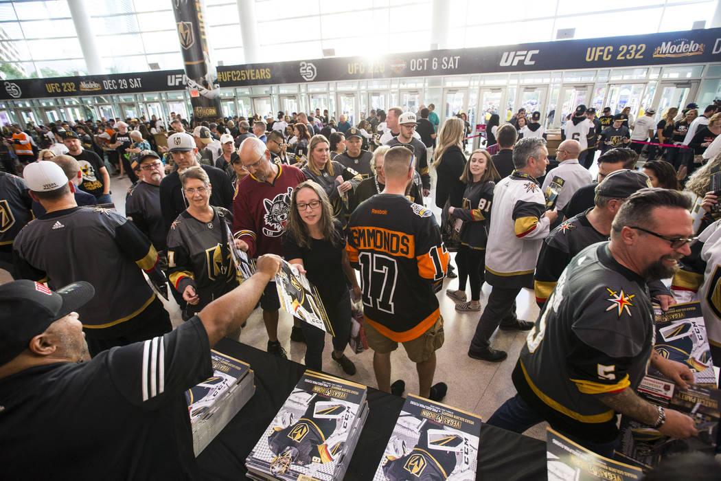 Los fanáticos del hockey reciben pósters antes de que los Golden Knights se enfrenten a los Philadelphia Flyers en su juego de apertura de temporada en T-Mobile Arena de Las Vegas el jueves 4 de ...