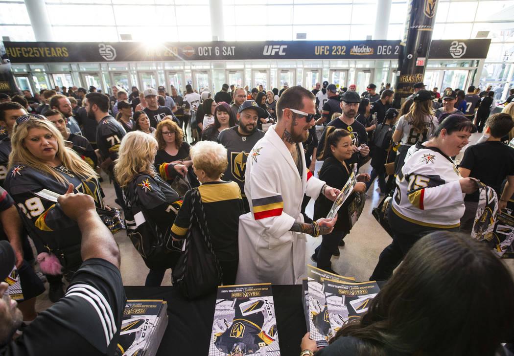 Un fanático del hockey en una bata de baño con temática de los Golden Knights, recibe un póster antes de que los Golden Knights se enfrenten a los Philadelphia Flyers en su primer partido de l ...