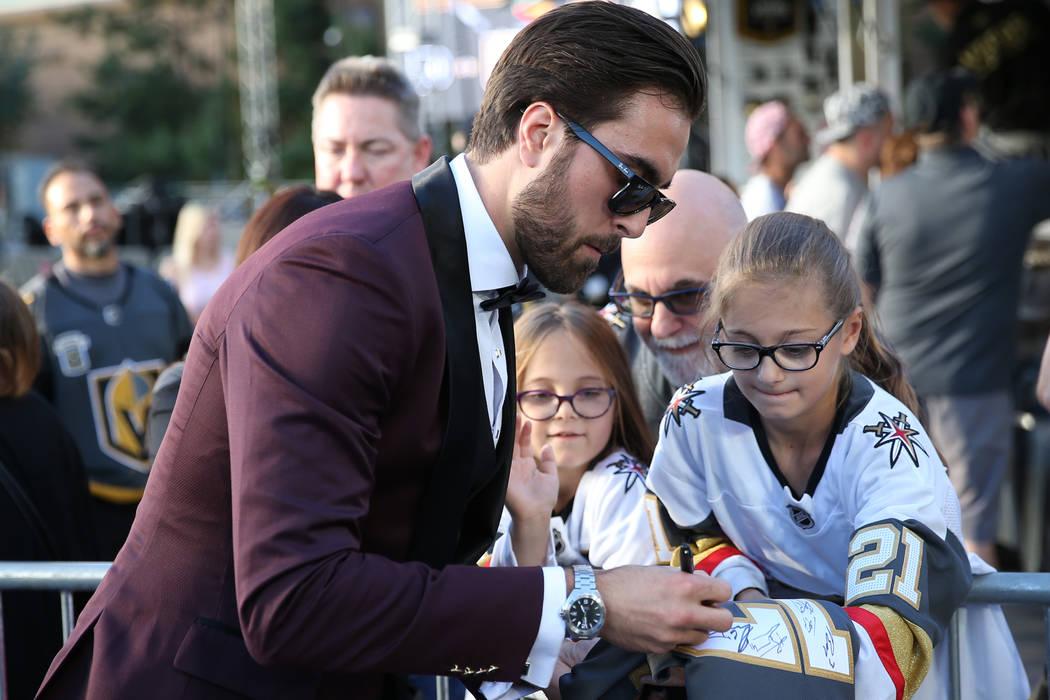 El alero derecho de los Golden Knights de Las Vegas, Alex Tuch (89), firma un autógrafo para Rebecca Staskin, de 10 años, a la derecha, con su hermana Emma, de 7 años, y el padre Michael de Las ...