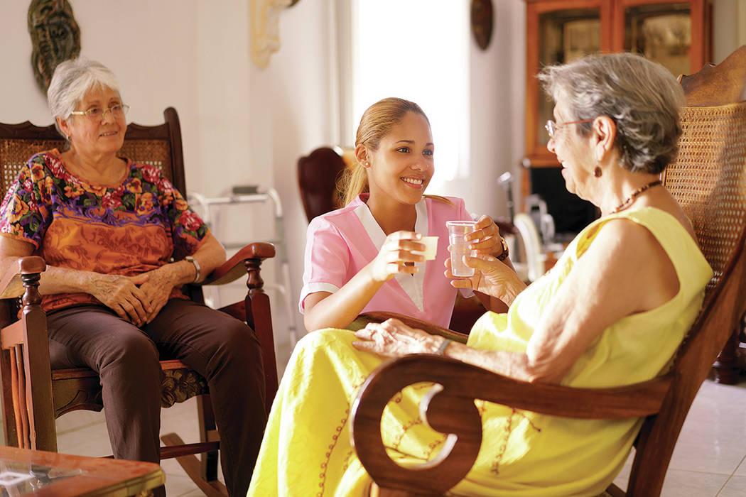 Personas mayores en un hospicio geriátrico: una joven hispana atractiva que como enfermera ayuda a una mujer mayor. Ella le da un vaso de agua y un medicamento recetado al paciente anciano. [ Fot ...