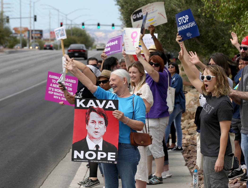 La gente saluda a los coches que pasan en un mitin que se opone a la confirmación del nominado a la Corte Suprema Brett Kavanaugh en las oficinas de For Nevada's Future en Las Vegas el sábado 6 ...