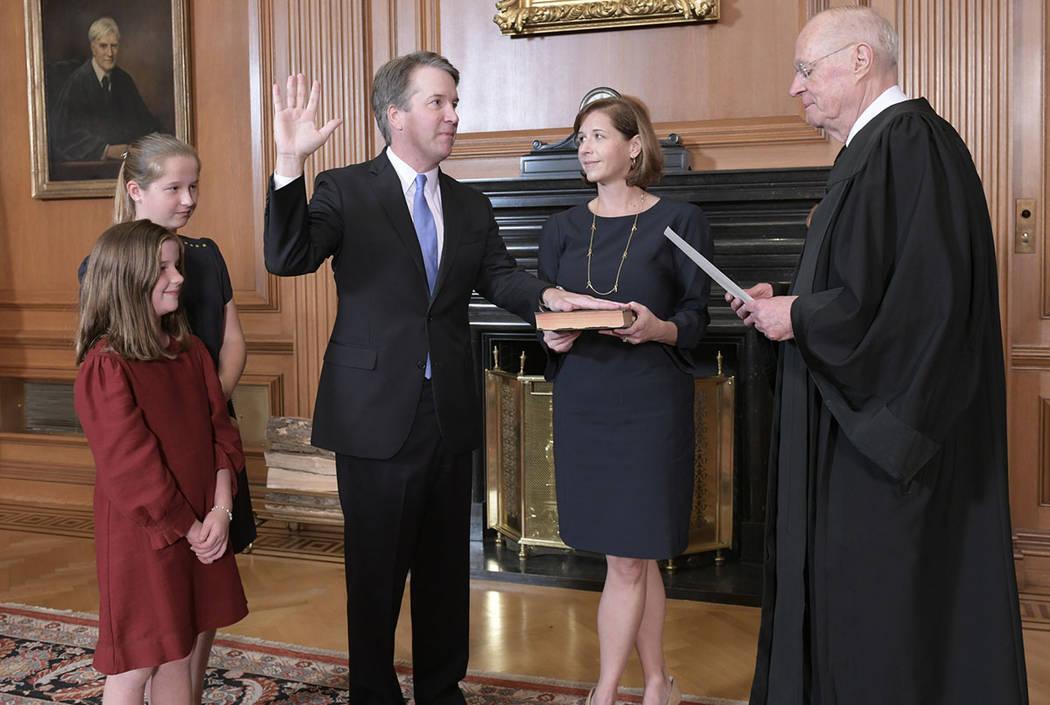 El juez retirado Anthony M. Kennedy, a la derecha, administra el juramento judicial al juez Brett Kavanaugh en la sala de conferencias de los jueces del edificio del Tribunal Supremo. Ashley Kavan ...
