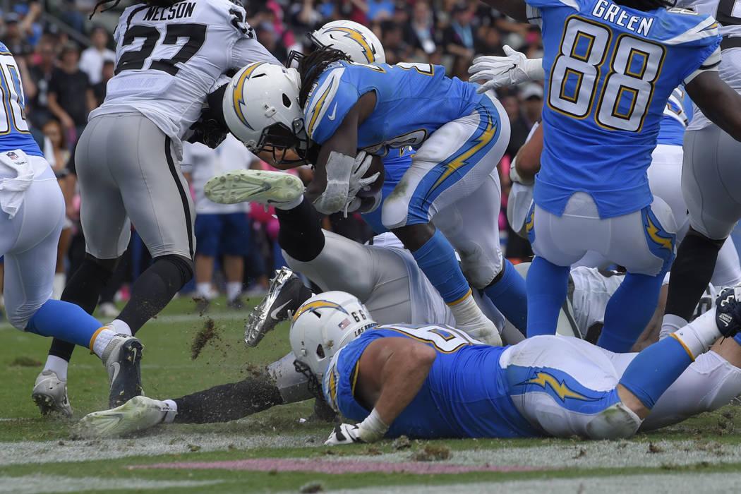El corredor de Los Ángeles Chargers, Melvin Gordon, centro, anotó un touchdown durante la primera mitad de un partido de fútbol de la NFL contra los Raiders de Oakland el domingo 7 de octubre d ...