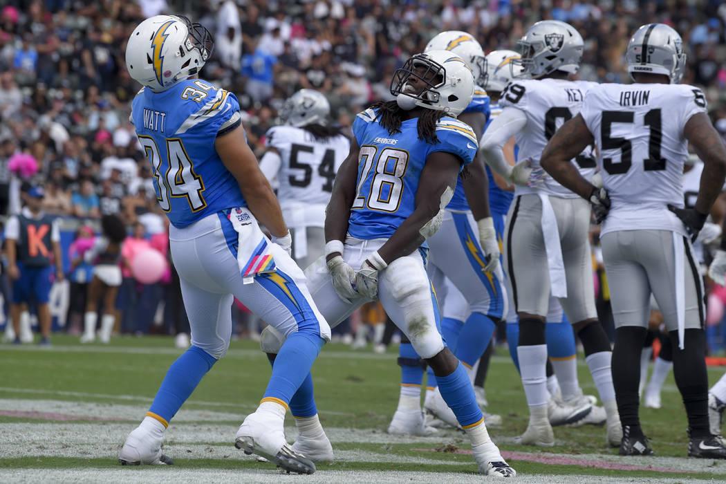 El corredor de Los Ángeles Chargers, Melvin Gordon (28) celebra su touchdown con su compañero de equipo Derek Watt (34), durante la primera mitad de un partido de fútbol de la NFL contra los Ra ...