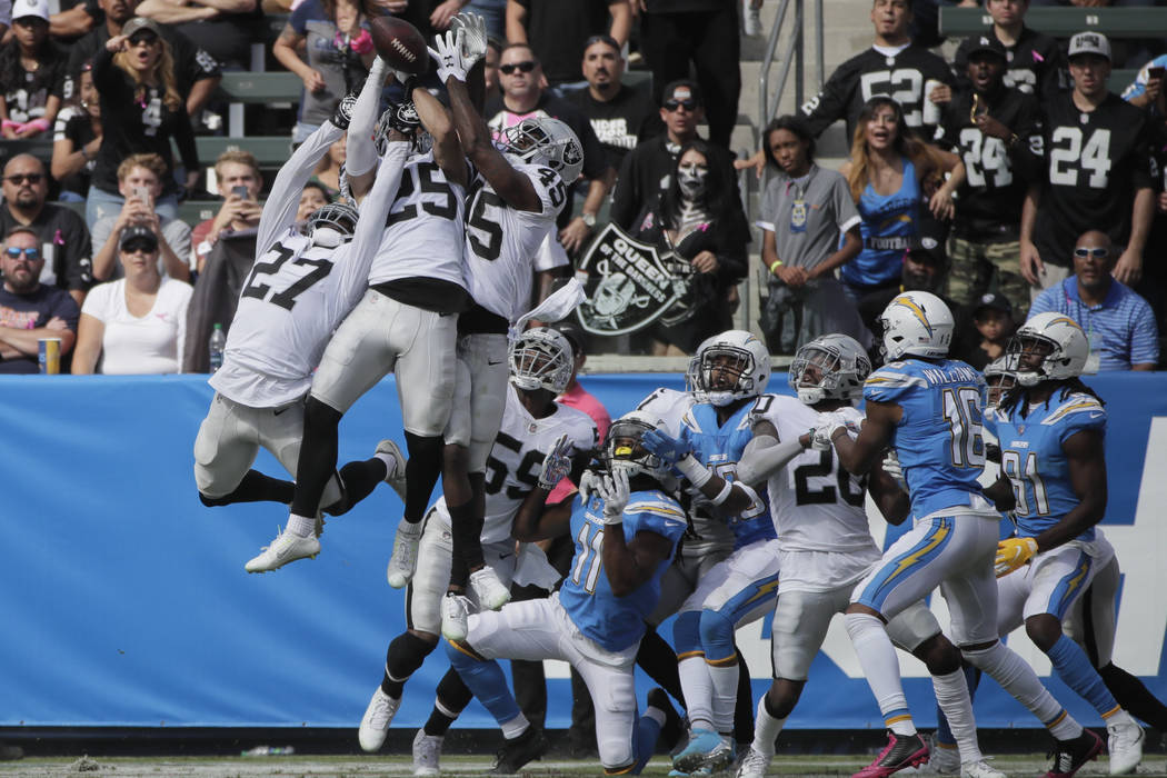 El defensa de los Raiders de Oakland, Erik Harris y otros, luchan por un lanzamiento en la zona final durante la primera mitad de un partido de fútbol de la NFL contra los Chargers de Los Ángele ...