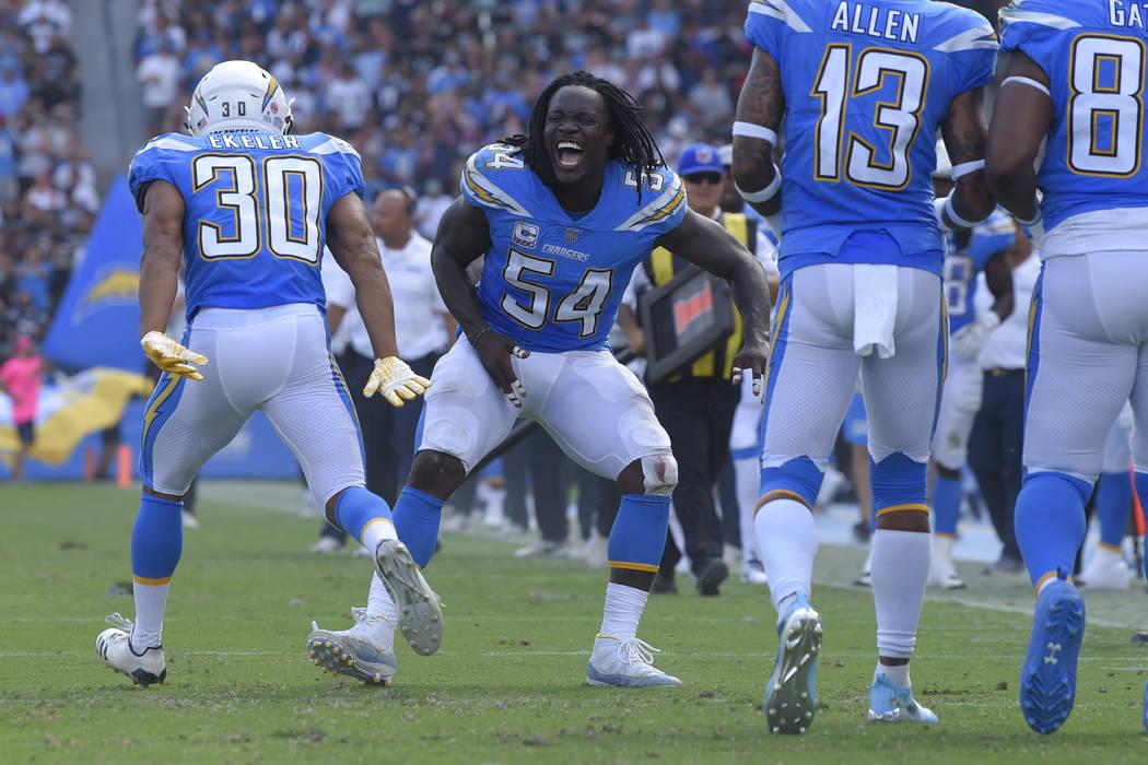 Melvin Ingram (54) de Los Ángeles Chargers, celebra con el corredor Austin Ekeler (30) luego de un touchdown de Ekeler durante la primera mitad de un partido de fútbol de la NFL contra los Raide ...