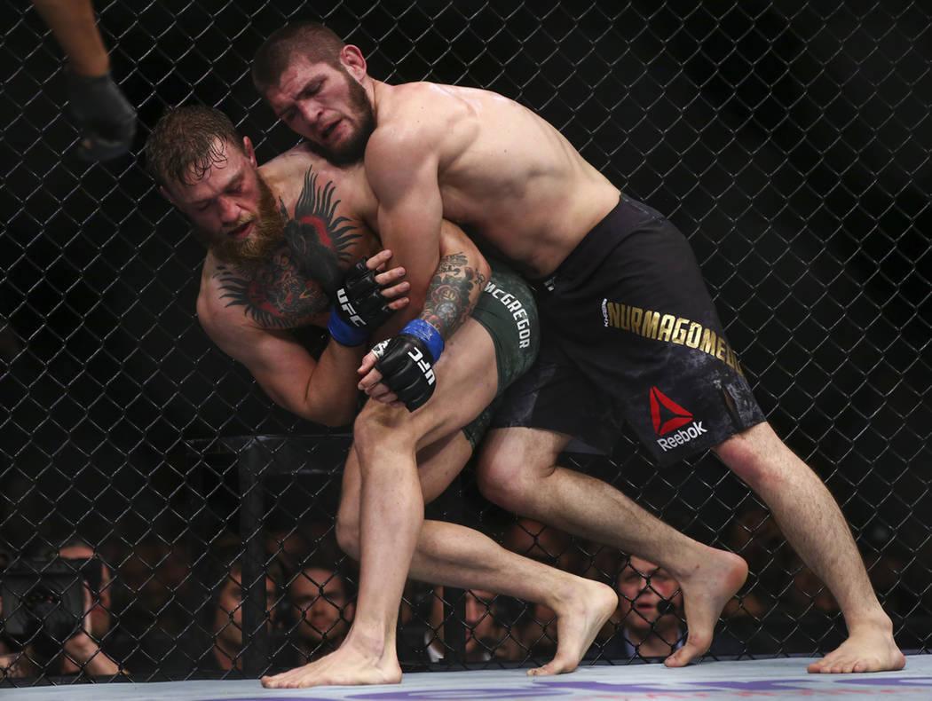 Khabib Nurmagomedov lleva a Conor McGregor a la lona durante su pelea por el título de peso ligero en el UFC 229 en el T-Mobile Arena de Las Vegas, el sábado 6 de octubre de 2018. Foto Chase Ste ...